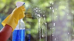 Jemand sprüht Reiniger an eine Fensterscheibe