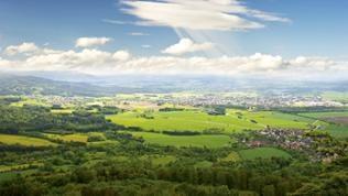 Hügelige Landschaft mit blauem Himmel und Wolken