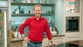 Moderator Martin Seidler in rotem Hemd in der Studioküche