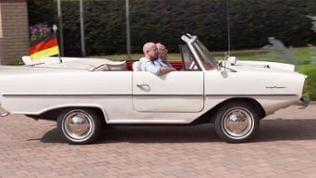 Oldtimer Fans in weißem Wagen mit Deutschland-Flagge am Heck