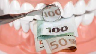 Vor einem Gebiss mis Zähnen liegen mehrere Euroscheine. In einem Zahnarztspiegel spiegelt sich die Zahl 100. (Foto: Getty Images, Getty Images)