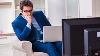 Ein Mann im Anzug mit einem Laptop auf dem Schoss schaut gebannt auf einen Fernseher (Foto: Colourbox)