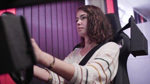 Junge brünette Frau am Steuer eines Fahrzeugsimulators in einer Fahrschule (Foto: SWR)