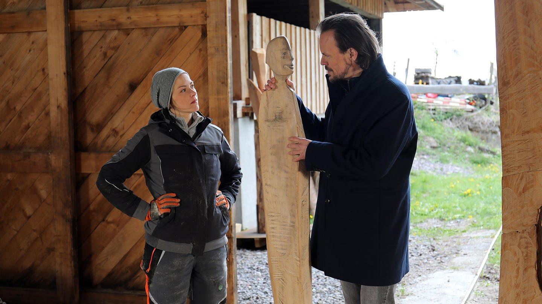 Sophie und Constantin stehen mit Sophies Holzskulptur am Eingang des Sägewerks (Foto: SWR, Johannes Krieg)