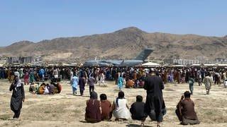 Afghanistan: Hunderte von Menschen versammeln sich in der Nähe eines Transportflugzeugs der US-Luftwaffe auf dem Flughafen in Kabul.  (Foto: dpa Bildfunk, picture alliance/dpa/AP / Foto Shekib Rahmani)
