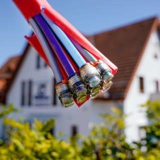 Ein Bündel mit Umhüllungen für Glasfaserkabel hängt an einem Schild und vor einem Wohnhaus.  (Foto: dpa Bildfunk, picture alliance/dpa | Uwe Anspach)