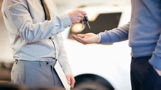 Ein Autoverkäufer übergibt einem Kunden einen Autoschlüssel. (Foto: Getty Images, Thinkstock -)