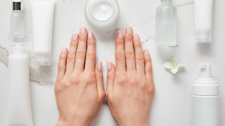 Hand liegt auf Tisch, daneben Tuben und Tigel (Foto: Colourbox)