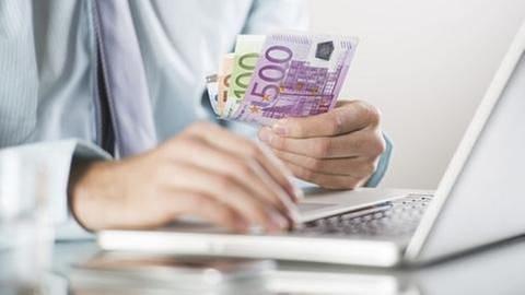 Ein Mann vor einem Laptop hält einige Euroscheine in der Hand | Getty Images, Thinkstock -