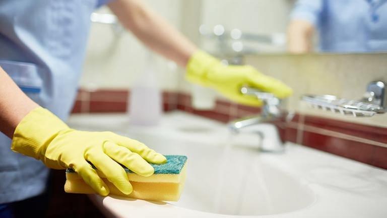 Mit einem Schwamm wird ein Badezimmer Waschbecken gereinigt. (Foto: Getty Images, Thinkstock -)