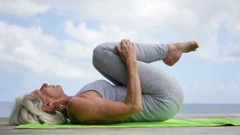 ältere Frau zieht die Beine bei einer Yoga-Übung an (Foto: Colourbox, Model Foto: Colourbox.de -)