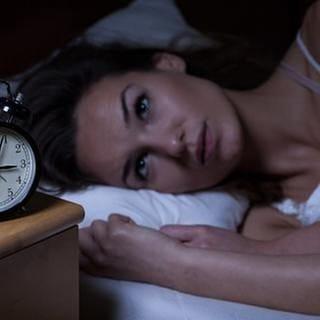 Frau liegt im Bett und schaut auf ihren Wecker der vier nach drei Uhr nachts zeigt. (Foto: Getty Images, Thinkstock -)
