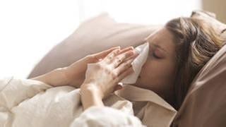 Eine Frau putzt sich die Nase, liegt krank im Bett (Foto: Getty Images, Thinkstock -)