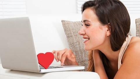 Lachende Frau liegt vor einem Laptop. Auf der Tastatur steht ein rotes Herz. (Foto: Getty Images, Thinkstock -)