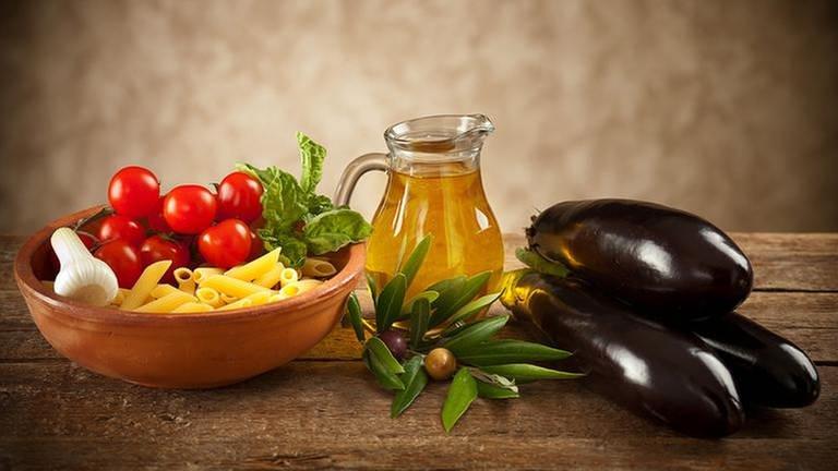 Auf einem Holztisch stehen Nudeln, Tomaten, ein Fläschchen Öl und Auberginen.