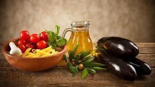 Auf einem Holztisch stehen Nudeln, Tomaten, ein Fläschchen Öl und Auberginen. (Foto: Colourbox, Foto: Colourbox.de -)