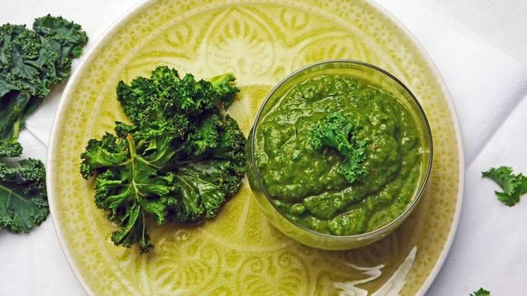 grüner teller mit glas mit grünem smoothie und grünkohlblätter daneben