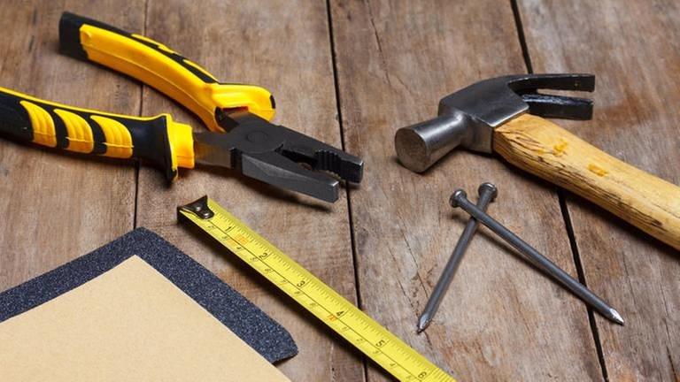 Verschiedene Werkzeuge wie Zange, Hammer, Nägel, Metermaß und Schleifpapier liegen auf einem Holztisch. (Foto: Colourbox, Foto: Colourbox.de -)