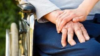 Eine junge Hand hält die Hand einer älteren Person im Rollstuhl. (Foto: Colourbox, Foto: Colourbox.de -)