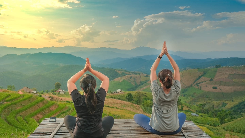 Zwei Frauen beim Yoga mit Blick auf die Berge (Foto: Colourbox)