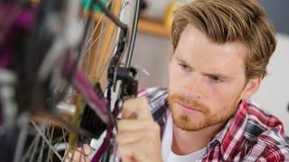 Man repariert ein Fahrrad (Foto: Colourbox)