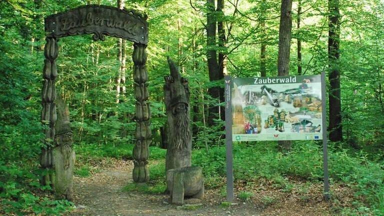 Eine Holzpforte steht am Rande eines Waldes
