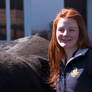 Betriebshelferin Chiara steht neben einer Kuh (Foto: SWR)
