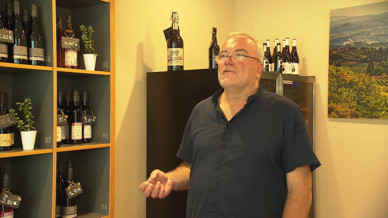 Mann steht vor Weinregalen