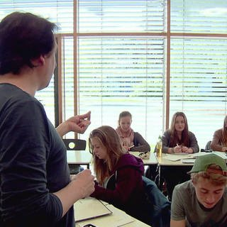 Lehrer steht vor seiner Schulklasse und spricht zu den Schülern (Foto: SWR)