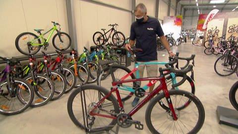 Fahrradhändler stellt Rad in einem Verkaufsraum auf (Foto: SWR)