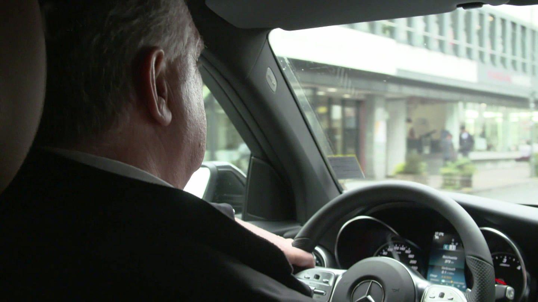 Fahrer am Steuer seines Wagens durch die Stadt fahrend (Foto: SWR)