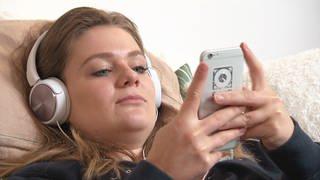 Junge Frau mit Kopfhörer und Handy (Foto: SWR)