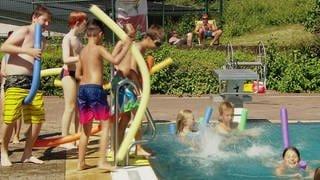 Kinder im Schwimmbad am Beckenrand und im Wasser (Foto: SWR)