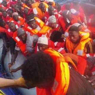 Schlauchboot voller Flüchtlinge wird von Rettungsschiff längsseite genommen. Flüchtling wird an Bord geholt (Foto: SWR)