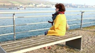 Pia Bauer sitzt nachdenklich am Rhein in Bingen: 2018 beging ihr Sohn Dirk Selbstmord. (Foto: SWR)