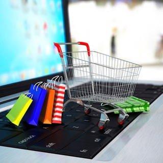 Ein Einkaufswagen und Einkaufstüten stehen auf einer Tastatur eines Laptops. (Foto: Getty Images, Thinkstock -)
