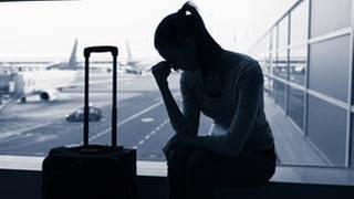 Eine Frau sitzt neben einem Koffer, verzweifelt mit dem Kopf auf eine Hand gestützt, vor einem Fenster am Flughafen. (Foto: Getty Images, getty images -)