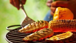 Auf einem Grillrost liegen ein Maiskolben, zwei Steks und eine Aubergine. Eine Hand hat einen Grillwender in der Hand und hebt damit ein Steak ab. (Foto: Colourbox)