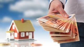 Eine Hand hält mehrere 50-Euro-Scheine in der Hand. Im Hintergrund ist ein EInfamilienhaus abgebildet. (Foto: Colourbox)