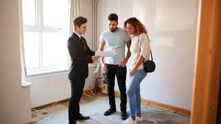 Ein Paar steht mit einem Makler in einer Wohnung und schaut auf ein Protokoll. (Foto: Colourbox)