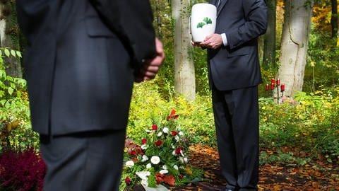Zwei Bestatter stehen mit einer Urne an einem Grab. (Foto: dpa Bildfunk, Picture Alliance/Oliver Dietze/dpa)