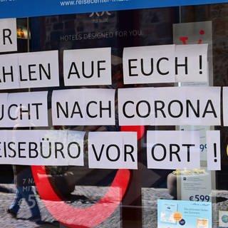 """in Reisebüro mit einem rieseigen Schaufenstensterschild auf dem steht: """"Wir zählen auf Euch! Bucht nach Corona im Reisebürovor Ort!""""  (Foto: dpa Bildfunk, picture alliance/Uwe Zucchi/dpa)"""