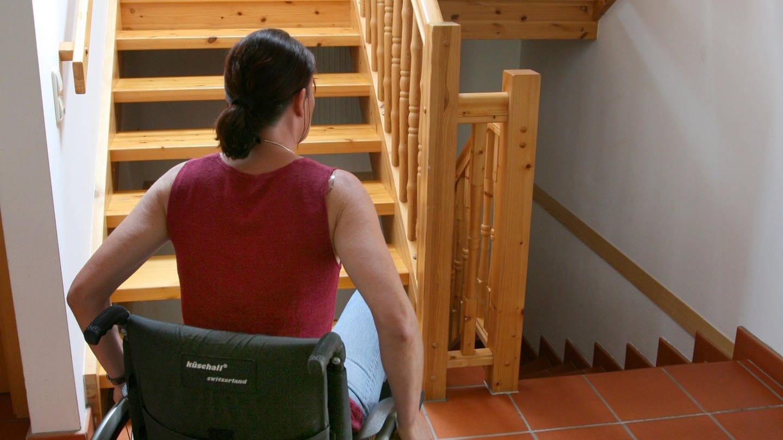 Frau im Rollstuhl vor Treppe, die nicht barrierefrei ist (Foto: Colourbox)