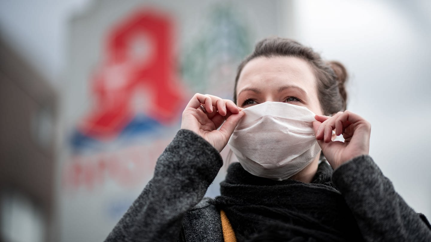 Eine Frau mit Mundschutz vor dem Gesicht (Foto: dpa Bildfunk, Fabian Strauch)