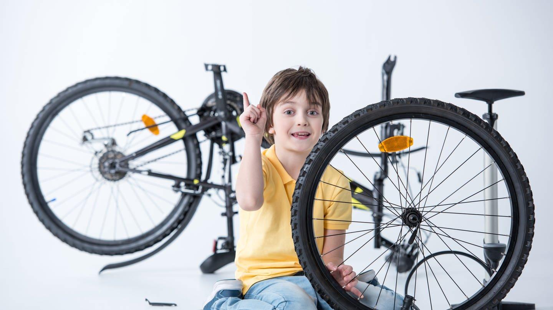 Kind beim Wechseln und Flicken eines platten Fahrradreifens
