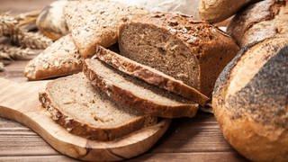 Auf einem Tisch liegen mehrere Scheiben Brot sowie Brötchchen. (Foto: Colourbox)