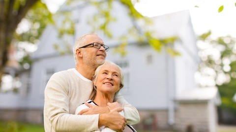 Glückliches älteres Paar hält sich vor einem Haus in den Armen: Mit einen barrierereduzierenden Umbau kann man länger Zuhause leben (Foto: Colourbox)