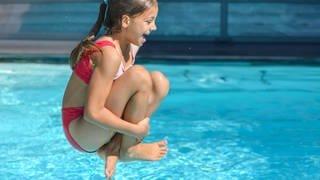 Bei sommerlich warmen 34 Grad Celsius springt ein Mädchen in einen Gartenpool.  (Foto: dpa Bildfunk, Picture Alliance)