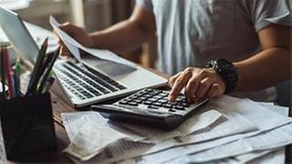 Ein Mann berechnetmit einem Taschenrechner die Kosten für seine Versicherung. (Foto: Colourbox, © Colourbox.de - torwai)