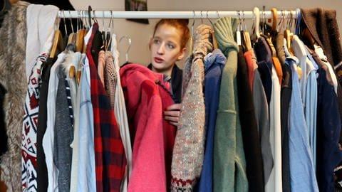 Junge Frau sortiert an ihrem Kleiderständer eine Jacke aus. (Foto: dpa Bildfunk, Roland Weihrauch)